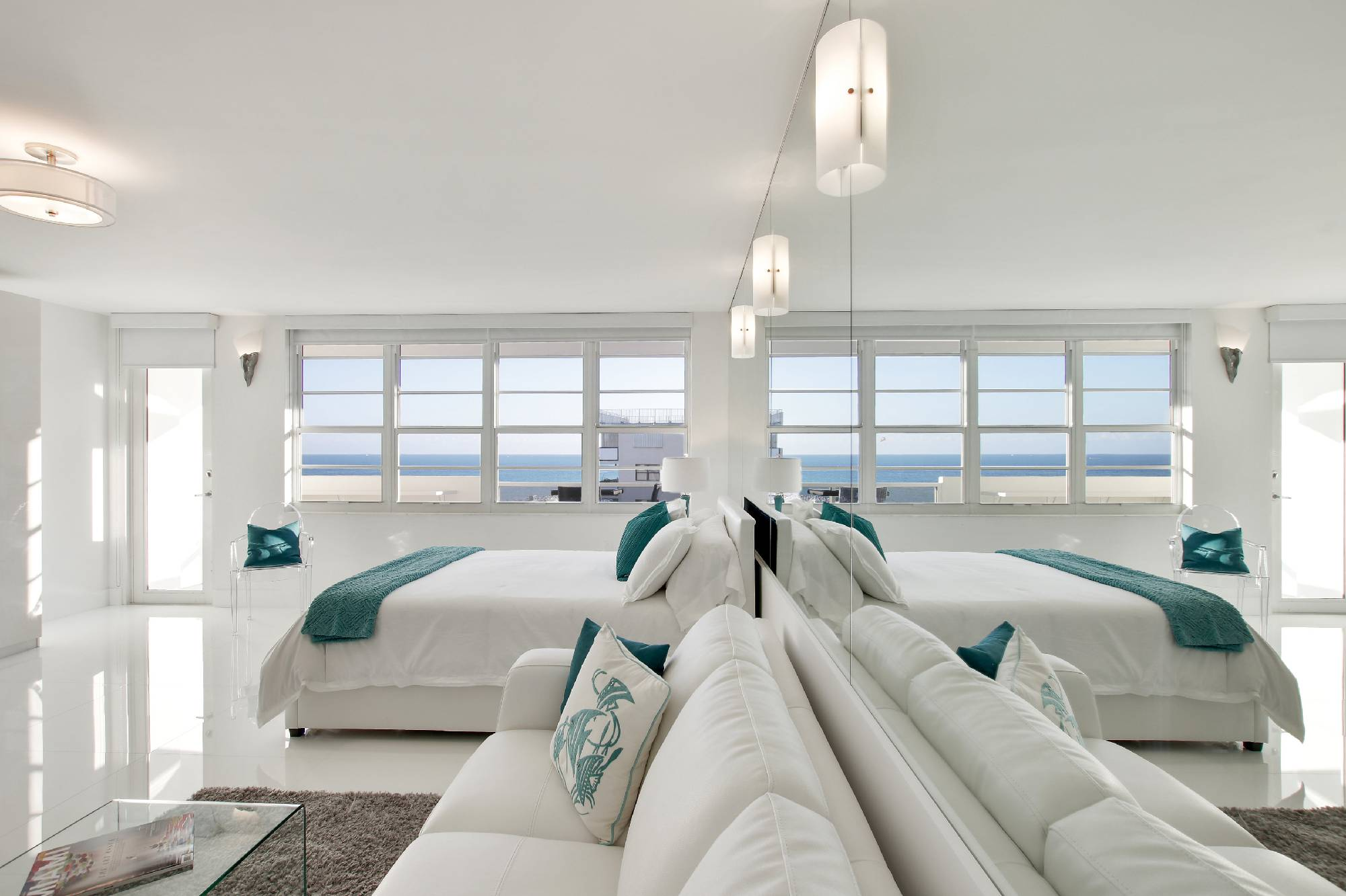 wide angle view of living room with mirrors and ocean view